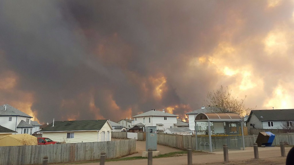 . Smoke rises from a wildfire outside of Fort McMurray, Alberta, Tuesday, May 3, 2016. The entire population of the Canadian oil sands city of Fort McMurray, has been ordered to evacuate as a wildfire whipped by winds engulfed homes and sent ash raining down on residents. (Mary Anne Sexsmith-Segato/The Canadian Press via AP)