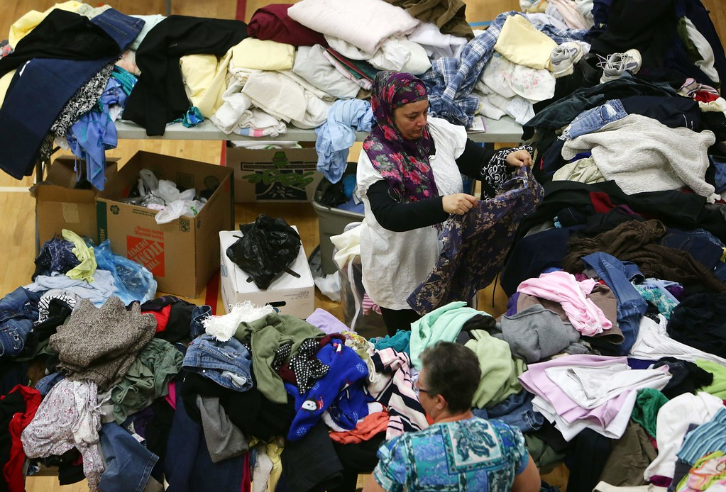 . A woman picks through donated clothing and goods at a makeshift evacuee center in Lac la Biche, Alberta on May 5, 2016, after fleeing forest fires north of Fort McMurray. Raging wildfires pressed in on the Canadian oil city of Fort McMurray Thursday after more than 80,000 people were forced to flee, abandoning fire-gutted neighborhoods in a chaotic evacuation. No casualties have been reported from the monster blaze, which swept across Alberta\'s oil sands region driven by strong winds and hot, dry weather.  / AFP PHOTO / Cole Burston/AFP/Getty Images