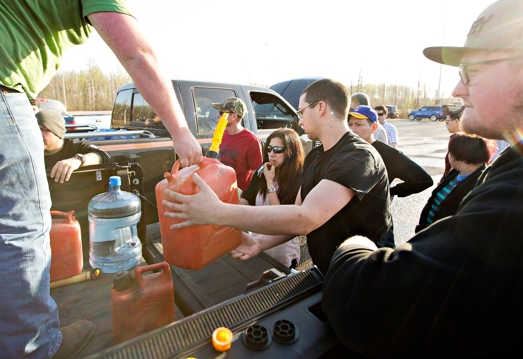 . People gather for gas that is being handed out at a rest stop near Fort McMurray, Alberta, Canada, on Wednesday, May 4, 2016. Thousands of residents were ordered to flee as flames moved into the Canadian oil sands city, destroying whole neighborhoods. (Jason Franson/The Canadian Press via AP)