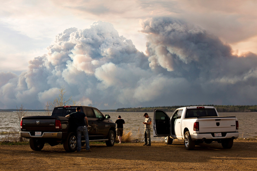 . Evacuees watch the wildfire near Fort McMurray, Alberta, on Wednesday, May 4, 2016. Alberta declared a state of emergency Wednesday as crews frantically held back wind-whipped wildfires.  No injuries or fatalities have been reported. (Jason Franson/The Canadian Press via AP)