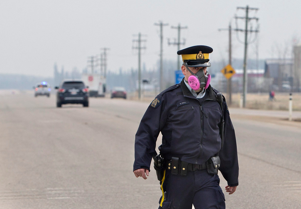 . A police officer wears a mask while controlling a roadblock near a wildfire in Fort McMurray, Alberta, Canada on Thursday, May 5, 2016.  Raging wildfires in the Canadian province of Alberta have moved south, forcing three more communities to evacuate and an emergency operations center to move again , aking it far from the devastated oil sands city of Fort McMurray. (Jason Franson/The Canadian Press via AP)