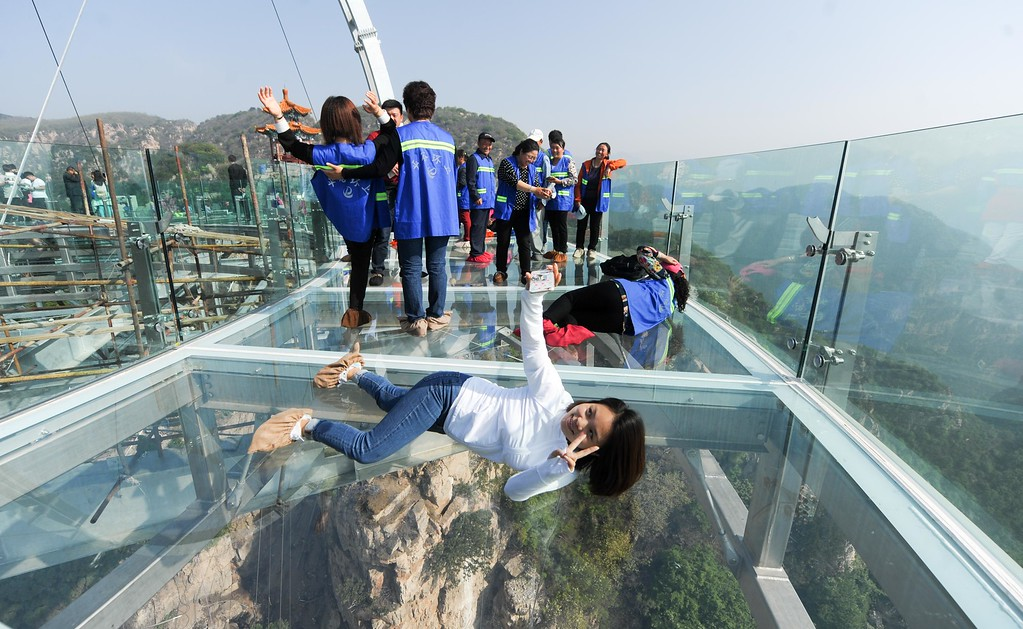 . This photo taken on April 30, 2016 shows people posing on a glass sightseeing platform in Shilinxia scenic spot in Pinggu District of Beijing.  The sightseeing platform, which hangs 32.8 meters out from the cliff, is claimed to be the largest glass sightseeing platform in the world. / AFP PHOTO / STR / /AFP/Getty Images
