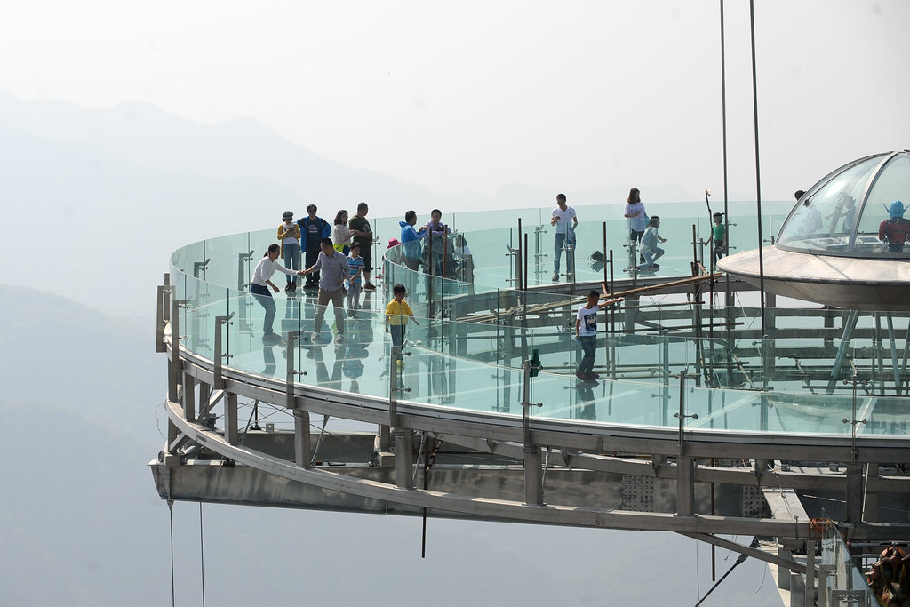 . This photo taken on April 30, 2016 shows people walking around a glass sightseeing platform in Shilinxia scenic spot in Pinggu District of Beijing.  The sightseeing platform, which hangs 32.8 meters out from the cliff, is claimed to be the largest glass sightseeing platform in the world. / AFP PHOTO / STR //AFP/Getty Images