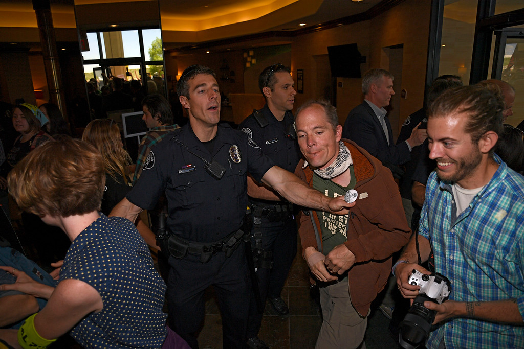. LAKEWOOD, CO - MAY 12: Hundreds of Colorado community, climate and fracking activists rush inside the lobby to the Holiday Inn as Lakewood PD tries to maintain order as the group protests a Bureau of Land Management oil and gas lease auction May 12, 2016 in Lakewood. The group rallied to disrupt the auction which was being held inside the hotel. The groups plan was to demand that public lands be no longer drilled, mined, or fracked. The protest was part of a global week of action focused on citizen action to keep fossil fuels in the ground and promote clean renewable energy, and comes days after the Colorado Supreme Court denied local authority to regulate fracking. (Photo By John Leyba/The Denver Post)