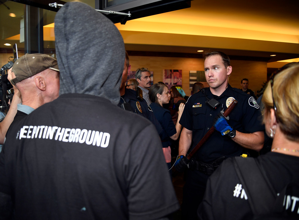 . LAKEWOOD, CO - MAY 12: Lakewood Police officer stands ground in the doorway of the Holiday Inn as Colorado community, climate and fracking activists try to disrupt a Bureau of Land Management oil and gas lease auction May 12, 2016 in Lakewood. The group rallied to disrupt the auction which was being held inside the hotel. The groups plan was to demand that public lands be no longer drilled, mined, or fracked. The protest was part of a global week of action focused on citizen action to keep fossil fuels in the ground and promote clean renewable energy, and comes days after the Colorado Supreme Court denied local authority to regulate fracking. (Photo By John Leyba/The Denver Post)