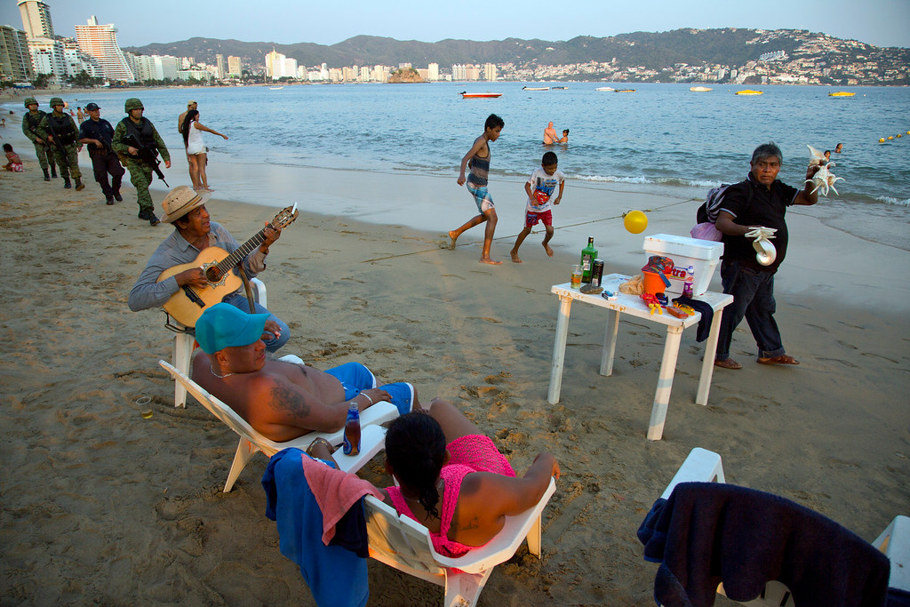 . In this May 11, 2016 photo, a roving seashell vendor walks past as a street musician serenades a local couple and marines along with local police patrol the shore of Papagayo Beach, in Acapulco, Mexico. Experts say Acapulco shows the limitations of the governmentís security strategy. Federal police, almost none of whom are from the city, quickly get lost once they leave the coastal boulevard and ascend into twisting, hillside neighborhoods. Their heavy weapons are ill-suited to urban policing. (AP Photo/Enric Marti)