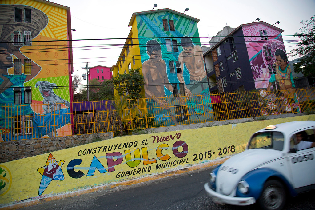 ". In this May 11, 2016 photo, a taxi drives past the Cuauhtemoc Housing Unit and a municipal sign with a message that reads in Spanish; ""Building the new Acapulco\"" in Acapulco, Mexico. The city\'s latest wave of killings began April 24, when bursts of gunfire broke out along the coastal boulevard. The murder rate in this city of 800,000 hit 146 per 100,000 inhabitants in 2012. It has since fallen to about 112 per 100,000, but that remains far higher than nationwide levels. (AP Photo/Enric Marti)"