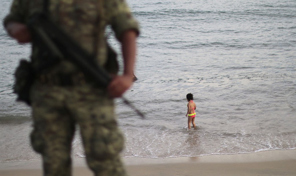 . A soldier stands guard as a girl stands on the shore of a beach in a touristic area of Acapulco, in the Mexican state of Guerrero, on October 27, 2015. Acapulco, once known as a celebrities refuge during the 50\'s, is now the city with the highest homicides rate in the country, where drug trafficking has flourished.   Pedro PARDO/AFP/Getty Images