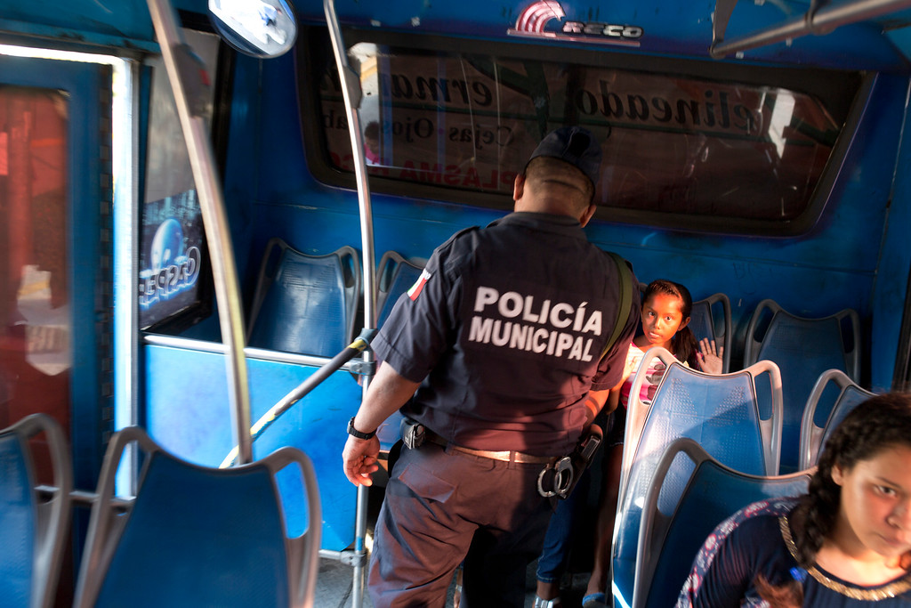 . In this May 10, 2016 photo, a girl riding a bus puts up her hands as a local policeman conducts a routine search at a checkpoint along the ìcostera,î the seaside boulevard that runs through the hotel zone in Acapulco, Mexico. An upsurge in killings has made Acapulco one of Mexicoís most violent places, scaring away what international tourism remained. In response, Mexico has lined the cityís coastal boulevard with heavily armed police and soldiers, but successes have been few. (AP Photo/Enric Marti)