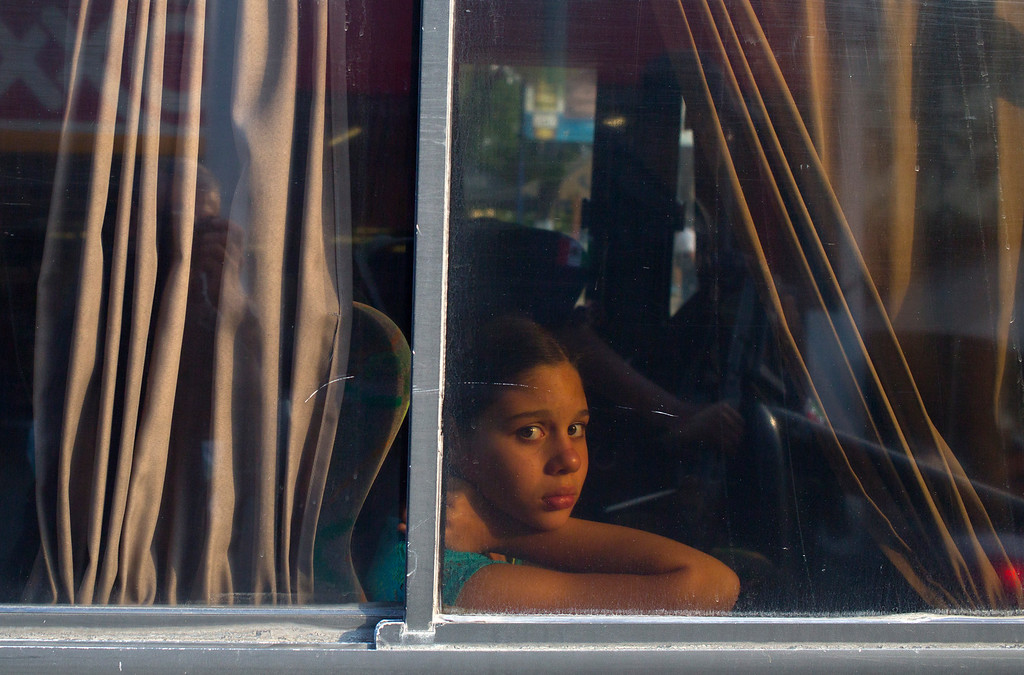 . In this May 10, 2016 photo, a girl stares out a bus window during a routine police checkpoint on the ìcostera,î the seaside boulevard that runs through the hotel zone in Acapulco, Mexico. Today itís almost easier to find a truck full of soldiers, a federal policeman or a gaggle of local tourist cops than it is to find a taxi along the seaside boulevard. (AP Photo/Enric Marti)