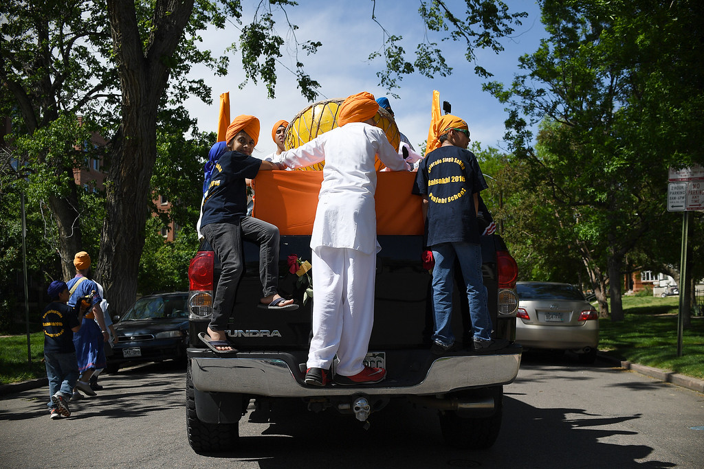 . DENVER, CO - MAY 22: Sikh youth ride on the back of a truck as a group of more than 1,000 Sikhs parade near 16th and High Street on Sunday, May 22, 2016. This was Denver\'s first ever Sikh parade. The event was held to celebrate the culture of the growing Sikh population in the area. (Photo by AAron Ontiveroz/The Denver Post)