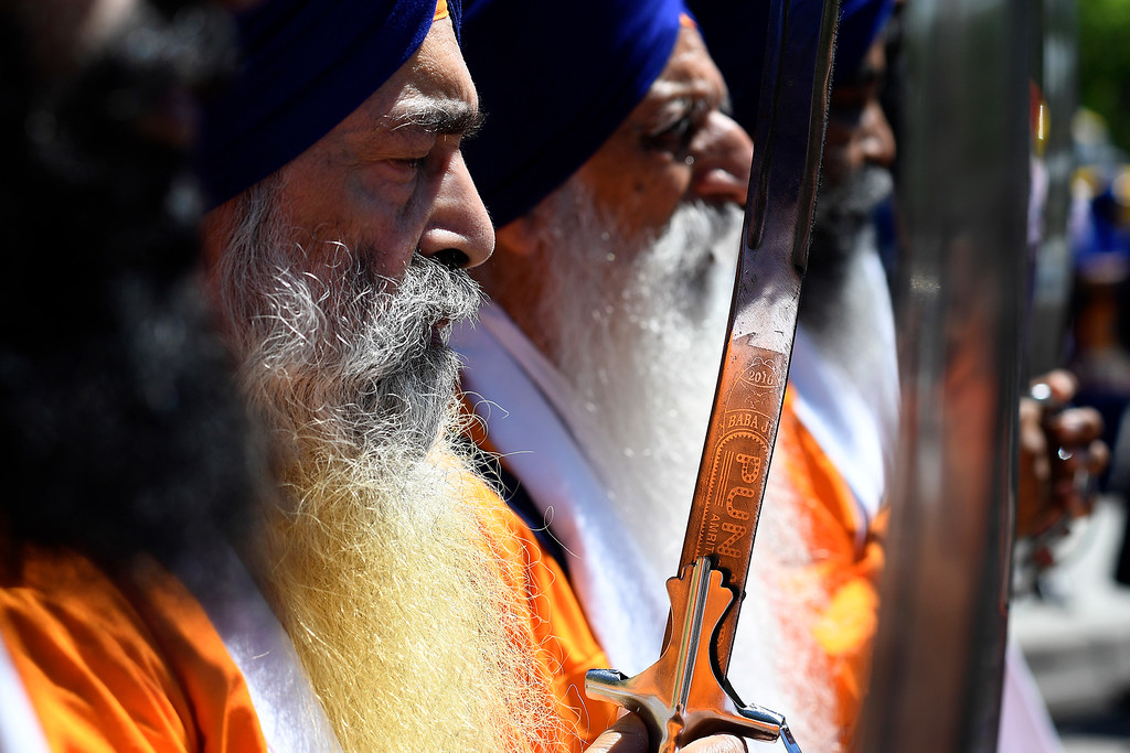 . DENVER, CO - MAY 22: Kultar Singh holds a saber as he stands with the Panjpiara � the group that leads the Guru Granth Sahib (Sikh scripture) � during  parade ceremony on Sunday, May 22, 2016. This was Denver\'s first ever Sikh parade. The event was held to celebrate the culture of the growing Sikh population in the area. (Photo by AAron Ontiveroz/The Denver Post)