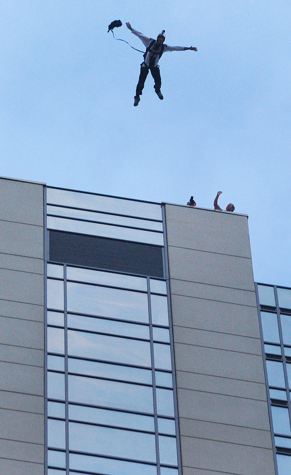 . Jeff Provenzano jumped from the roof and did a free fall for several seconds. BASE jumpers Miles Daisher and Jeff Provenzano lept off the top of the Four Seasons Hotel in downtown Denver Tuesday night, August 27, 2013 before they each deployed a canopy to make a safe landing in the parking lot.   Photo By Karl Gehring/The Denver Post