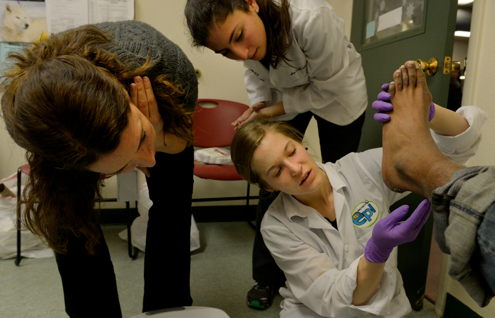 . Medical student, Amy Beeson, examines Jason Smith\'s foot with  nurse practitioner student, Ana Calderon, top, and assistant professor Jennifer Caragol during the CU UNITE Foot Care Clinic at the St. Francis Center in Denver, CO March 01, 2014. (Photo By Craig F. Walker / The Denver Post)