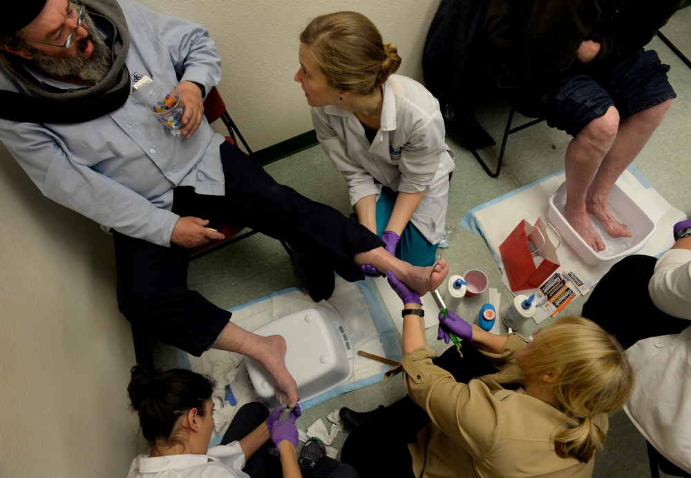 ". Marc Allen, top left, receives treatment from medical student, Amy Beeson, top right, nurse practitioner student, Ana Calderon, bottom left, and nurse practitioner faculty member, Jan Beezley during the CU UNITE Foot Care Clinic at the St. Francis Center in Denver, CO March 01, 2014. Students and staff from University of Colorado health care programs offered foot care to the homeless and the needy at the St. Francis Center, Samaritan House and the Denver Rescue Mission on Saturday. In doing so the students from the University of Colorado School of Medicine, the CU College of Nursing nurse practitioner programs and the Physician Assistant program receive training in working with urban underserved communities. Allen said he has arthritis in his feet and greatly appreciates the service, ""God bless them, thank you, thank you, thank you.\"" (Photo By Craig F. Walker / The Denver Post)"