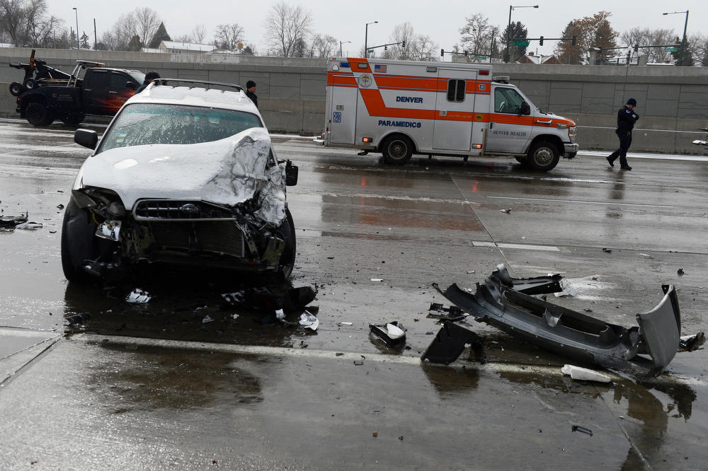 . Denver Fire and Police clean up the scene of a multi-vehicle crash on north bound I-25 at Downing St. Saturday morning, March 01, 2014. According to Denver Police, crashes also occurred farther north on I-25 at Logan and also at Broadway, over 40 cars and trucks total were involved, approximately 20 people were hospitalized and one person died at the Logan crash scene.  (Photo By Andy Cross / The Denver Post)