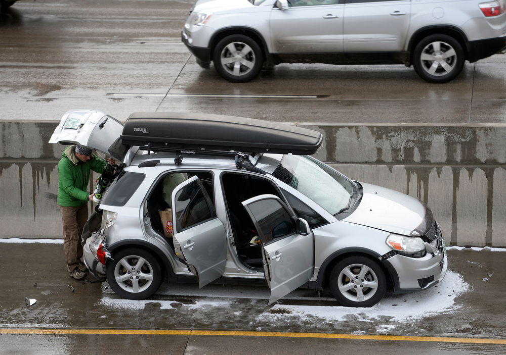 . As traffic moves south bound above him, a man involved in the accident goes through his belongings in his car. One person was killed and 20 people were taken to three hospitals with injuries Saturday morning in a giant pileup on north bound Interstate 25 as a band of heavy snow moved through Denver. (Photo by Kathryn Scott Osler/The Denver Post)