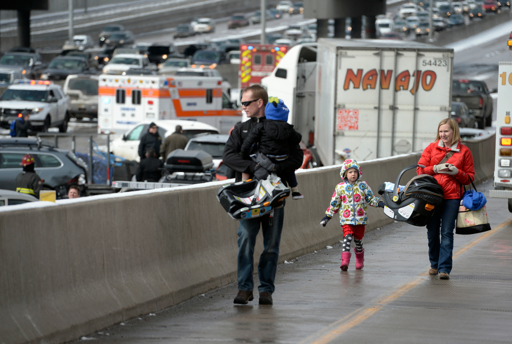 . A family involved in the accident, who didn\'t want to give their names, walk up the on ramp that leads from South Washington Street on to I-25. One person was killed and 20 people were taken to three hospitals with injuries Saturday morning in a giant pileup on north bound Interstate 25 as a band of heavy snow moved through Denver. (Photo by Kathryn Scott Osler/The Denver Post)
