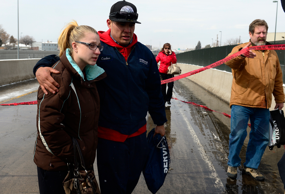 . Mariah Davila, left, puts her arm around her husband Carlos who was involved in the accident on I-25. Carlos was driving his Subaru home from work and his car became sandwiched between two cars, the car in front of him ended up on top of the front of his car. One person was killed and 20 people were taken to three hospitals with injuries Saturday morning in a giant pileup on north bound Interstate 25 as a band of heavy snow moved through Denver. (Photo by Kathryn Scott Osler/The Denver Post)