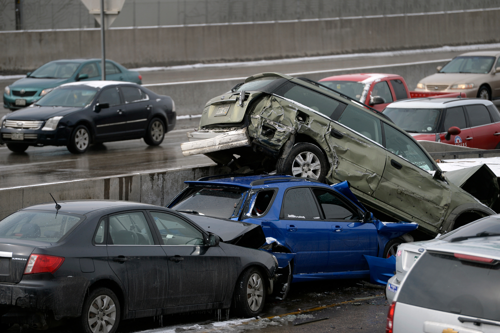 . Carlos Davila\'s blue Subaru can be seen sandwiched between two other cars. One person was killed and 20 people were taken to three hospitals with injuries Saturday morning in a giant pileup on north bound Interstate 25 as a band of heavy snow moved through Denver. (Photo by Kathryn Scott Osler/The Denver Post)