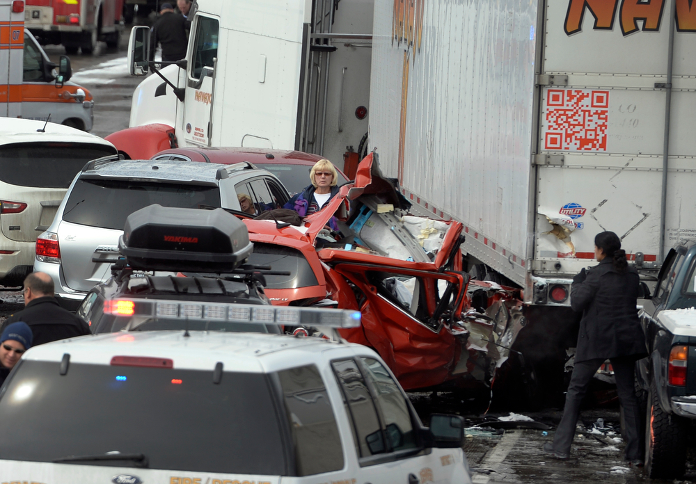 . A woman peers over the orange/red colored car in which the fatality occurred. One person was killed and 20 people were taken to three hospitals with injuries Saturday morning in a giant pileup on north bound Interstate 25 as a band of heavy snow moved through Denver. (Photo by Kathryn Scott Osler/The Denver Post)