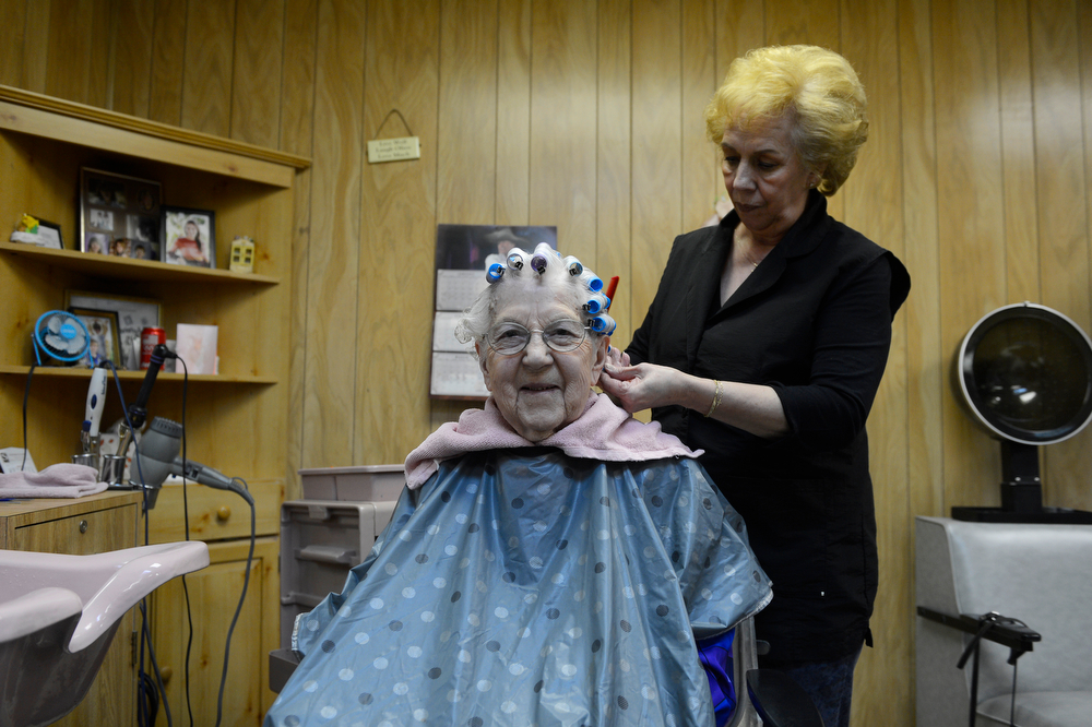 . LITTLETON, CO. - MARCH 26:  Hairstylist, Nancy Evans, right, takes out curlers from Arlene Molis\' hair at New Creations hair salon Wednesday afternoon, March 26, 2014. Molis, 95-years-old, gets her hair done weekly at the salon, getting a ride from volunteers at the Columbine Community Village. (Photo By Andy Cross / The Denver Post)
