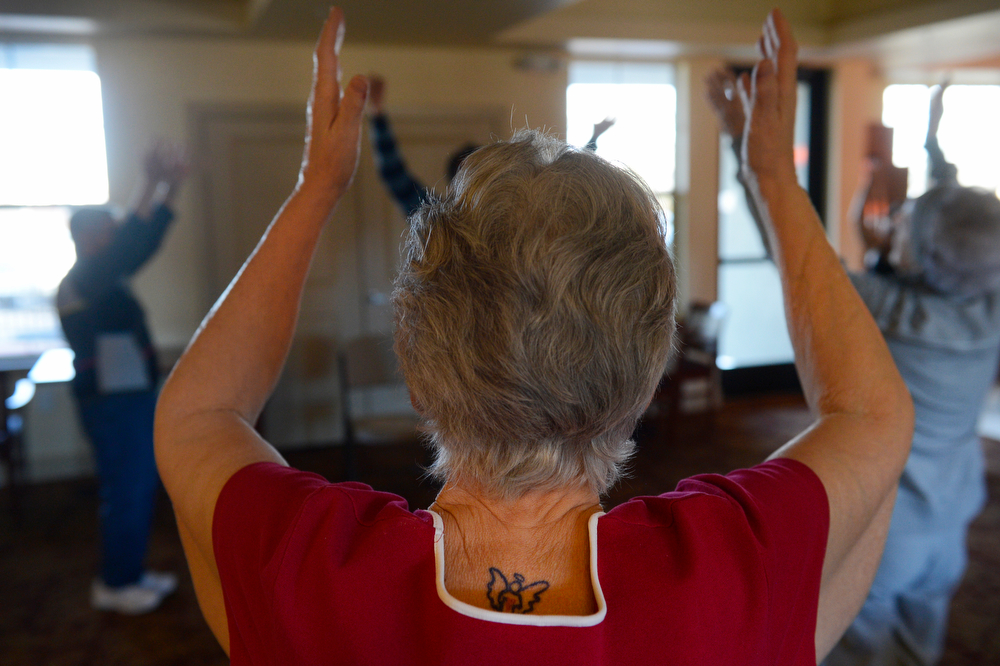 . WHEAT RIDGE, CO. - MARCH 20: Sandy Soderberg, 67, sporting an angel tattoo on the back of her neck, raises her arms during a Tai Chi class at the Wheat Ridge Town Center Apartments, a new senior housing community, Thursday morning, March 20, 2014. The center offers a variety of on-site activities including coffee bar, Tai Chi, Wii bowling, fitness room, and gardening. (Photo By Andy Cross / The Denver Post)