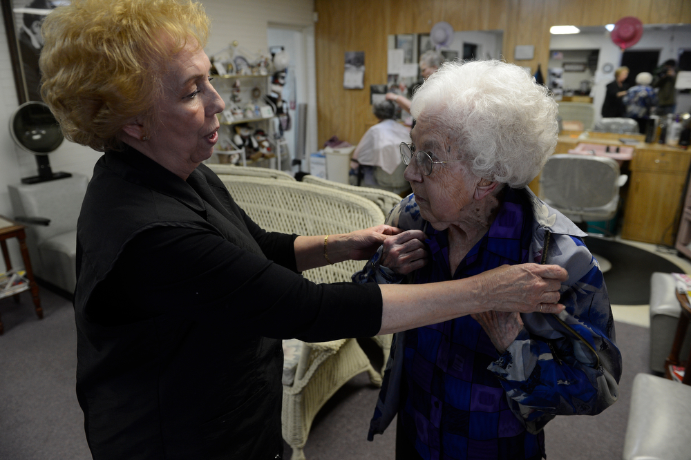 . LITTLETON, CO. - MARCH 26:  Hairstylist, Nancy Evans, left, makes sure that friend and and client, Arlene Molis, 95, has her jacket on properly after doing her hair at the New Creations hair salon Wednesday afternoon, March 26, 2014. Molis, 95-years-old, gets her hair done weekly at the salon, getting a ride from volunteers at the Columbine Community Village. (Photo By Andy Cross / The Denver Post)