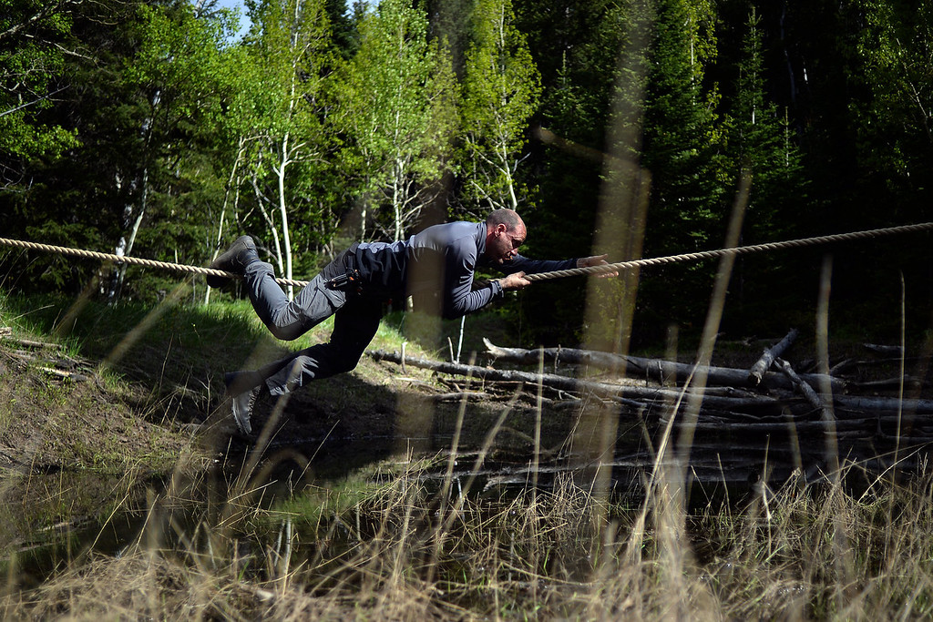 . WARD, CO - JUNE 10: Matthew Bragg climbs across a rope bridge. Bear Grylls survival school at Glacier View Ranch near Ward, Colorado on Tuesday, June 10, 2014. (Photo by AAron Ontiveroz/The Denver Post)