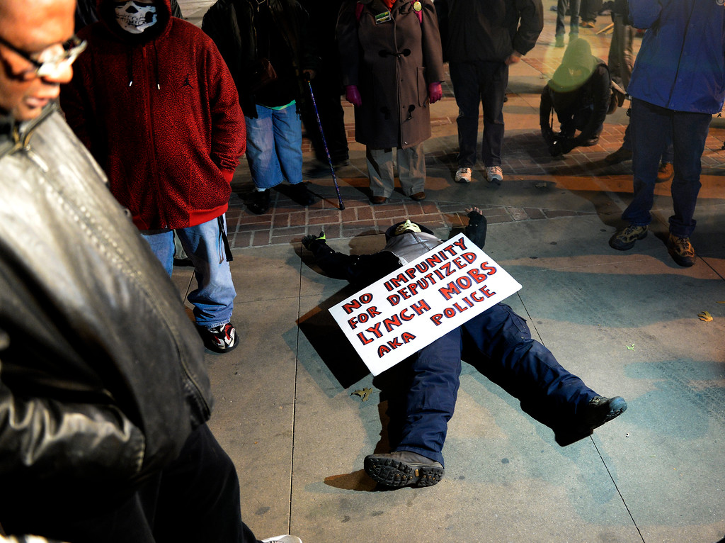 . A protester lays on the ground during a moment of silence as they gather on the sidewalk at Broadway at Civic Center Park after learning a Grand jury decided November 24, 2014 not to indict Ferguson police officer Darren Wilson in Michael Brown\'s death on August 9, 2014. (Photo By John Leyba/The Denver Post)