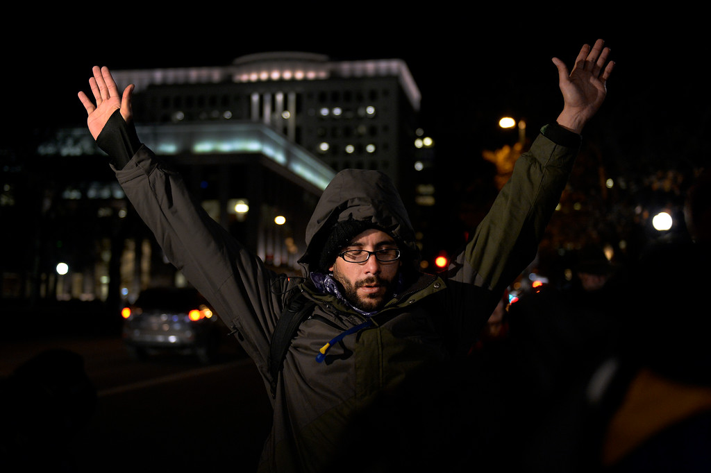 . Gary Rowland 35, of Boulder, holds his arms up in a moment of silence as they gather on the sidewalk at Broadway at Civic Center Park after learning a Grand jury decided November 24, 2014 not to indict Ferguson police officer Darren Wilson in Michael Brown\'s death on August 9, 2014. (Photo By John Leyba/The Denver Post)