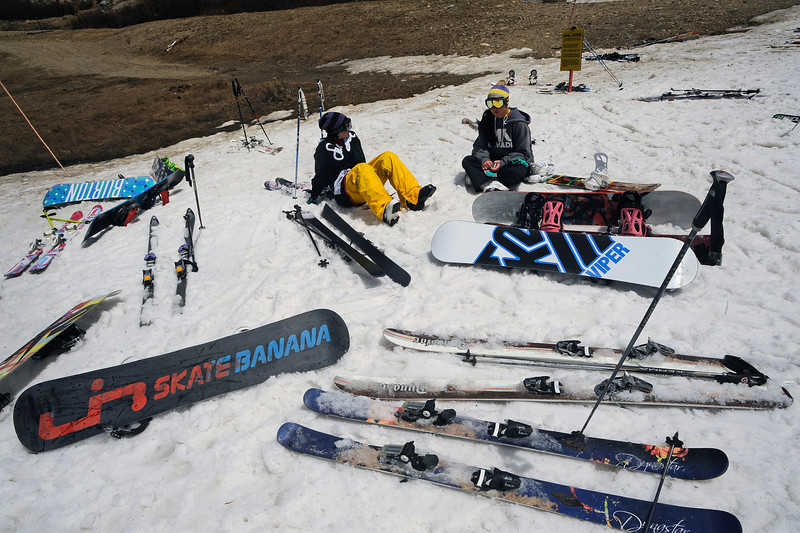 Maggie Dufficy, 20 of Boulder, in yellow pants, and Victoria Chen, 19, right of Westminster, relax in the snow and enjoy the sun after a day of snowboarding.<br /> Today, May 6th, 2012, Arapahoe Basin will be the last Colorado Ski resort to close for the season.  Typically, the resort stays open well into the summer closing last year on July 4th.  But with the dismal year for snow and almost no snow left on the slopes the ski area decided to call it quits for the year.<br /> Helen H. Richardson, The Denver Post