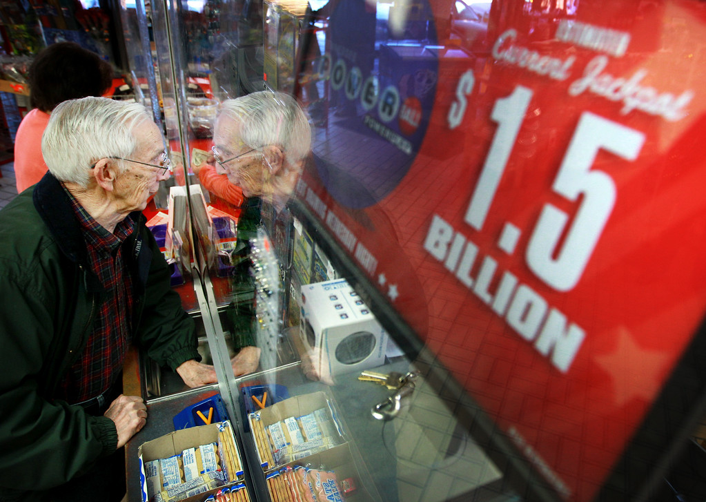 . Tony Floyd passes his money through the window while purchasing a Powerball ticket at the Elvis Presley BP near the state line in Memphis, Tenn., Tuesday, Jan. 12, 2016. The convenience store is said to be the busiest lottery location in Shelby County. (Mike Brown/The Commercial Appeal via AP)