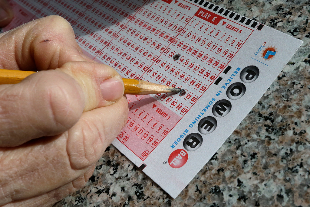 . A lottery player fills out numbers on a Powerball form Tuesday, Jan. 12, 2016, in Oakland, Calif. The Powerball jackpot has grown to over 1.5 billion dollars. (AP Photo/Ben Margot)