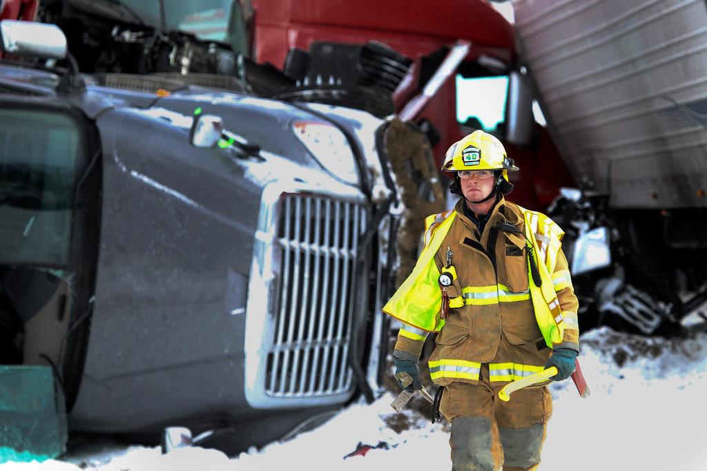 . An officer walks away from a fatal crash scene near Fredericksburg, Pa., Saturday, Feb. 13, 2016. State police say a pileup has closed Interstate 78 in central Pennsylvania. (Daniel Zampogna/PennLive.com via AP)