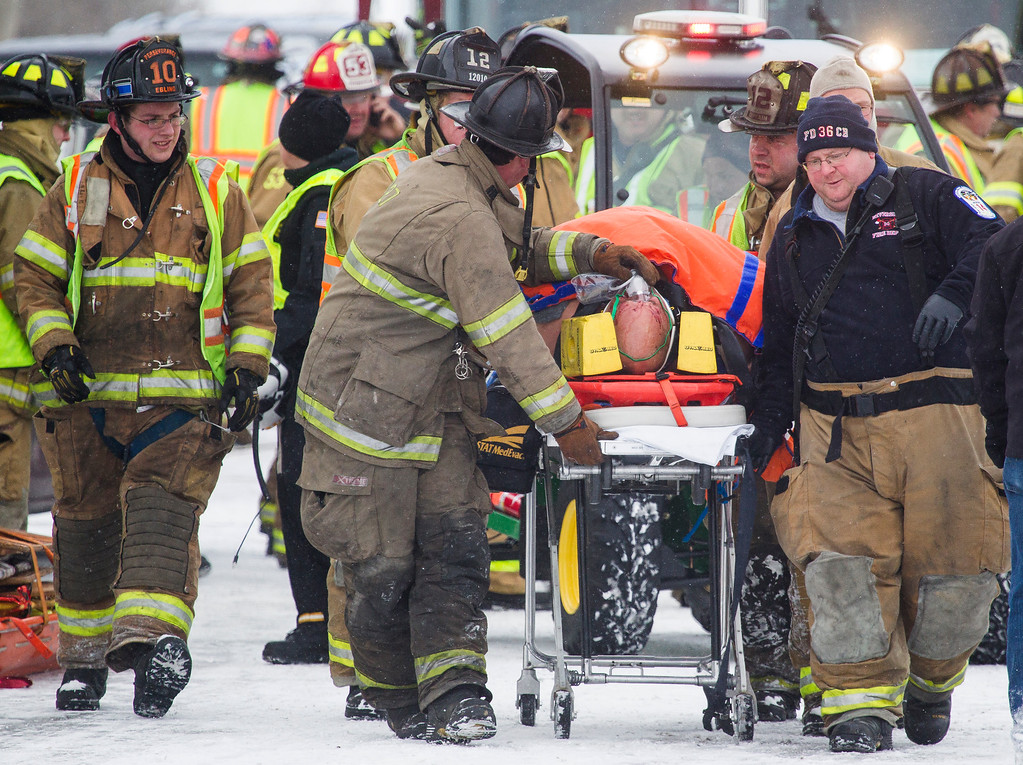 . Emergency personnel carry someone away from a fatal crash scene near Fredericksburg, Pa., Saturday, Feb. 13, 2016. The pileup left tractor-trailers, box trucks and cars tangled together across several lanes of traffic and into the snow-covered median. (Daniel Zampogna/PennLive.com via AP)