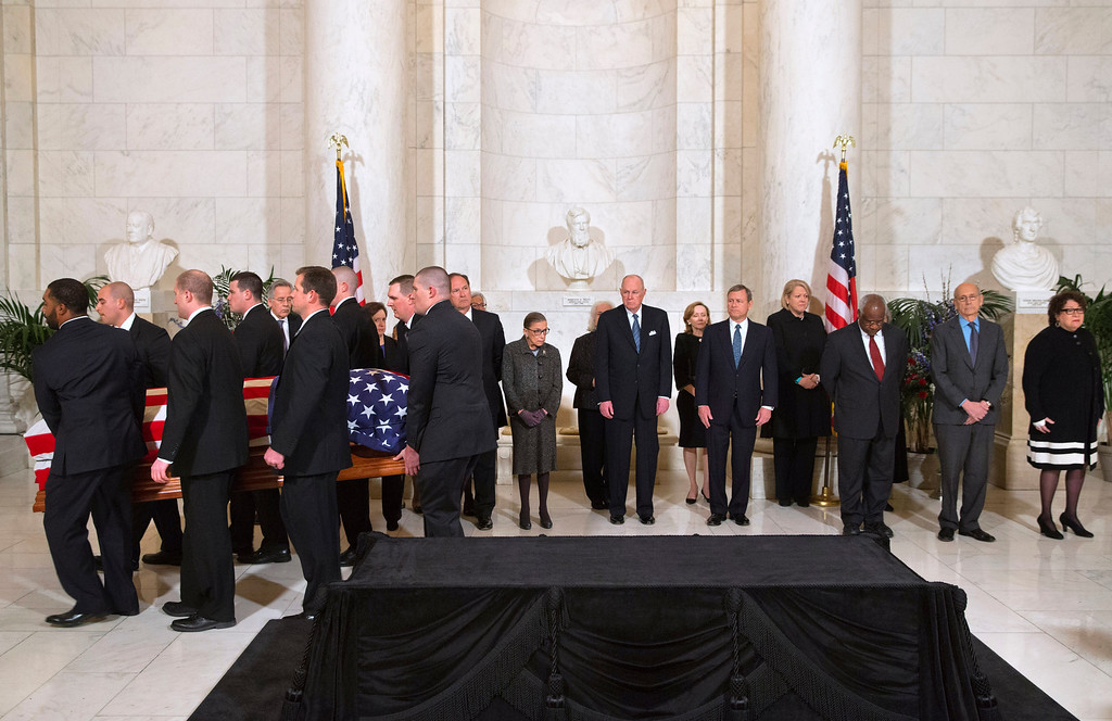 . The casket of late Supreme Court Justice Antonin Scalia is carried into the Great Hall of the Supreme Court for a private ceremony in Washington, Friday Feb. 19, 2016, past Supreme Court Justices from back left Counselor to the Chief Justice Jeffrey Minear, and Supreme Court Justices Elena Kagan, Samuel Anthony Alito, Jr., Ruth Bader Ginsburg, Anthony Kennedy, Chief Justice John Roberts, Jr., Clarence Thomas, Stephen Breyer, and Sonia Sotomayor. (AP Photo/Jacquelyn Martin, Pool)