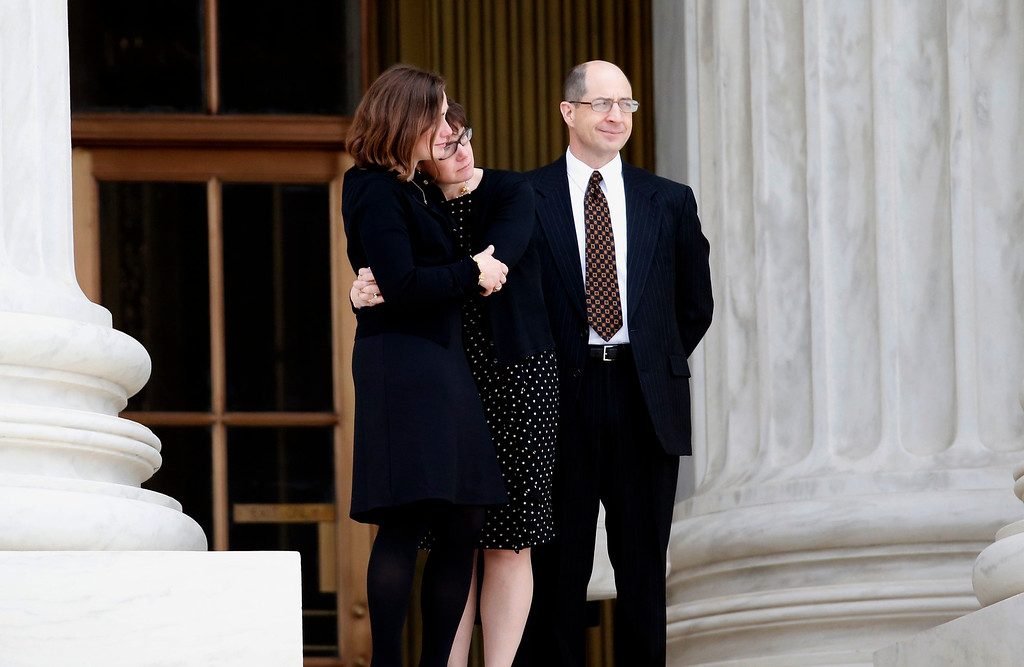 . People comfort each other at the top of the steps of the Supreme Court in Washington, Friday, Feb. 19, 2016, as they look at the lines of people waiting to view the body of Justice Antonin Scalia. Thousands of mourners will pay their respects Friday for Justice Antonin Scalia as his casket rests in the Great Hall of the Supreme Court, where he spent nearly three decades as one of its most influential members. (AP Photo/Alex Brandon)