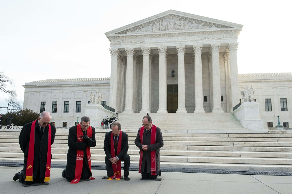 . Members of the National Clergy Council pray for US Supreme Court Justice Antonin Scalia before the arrival of his casket in Washington, DC, on February 19, 2016 where it will lie in state until his funeral at the Basilica of the National Shrine of the Immaculate Conception on February 20. Scalia died on February 13 at the age of 79. / AFP / Nicholas  KAMM/AFP/Getty Images