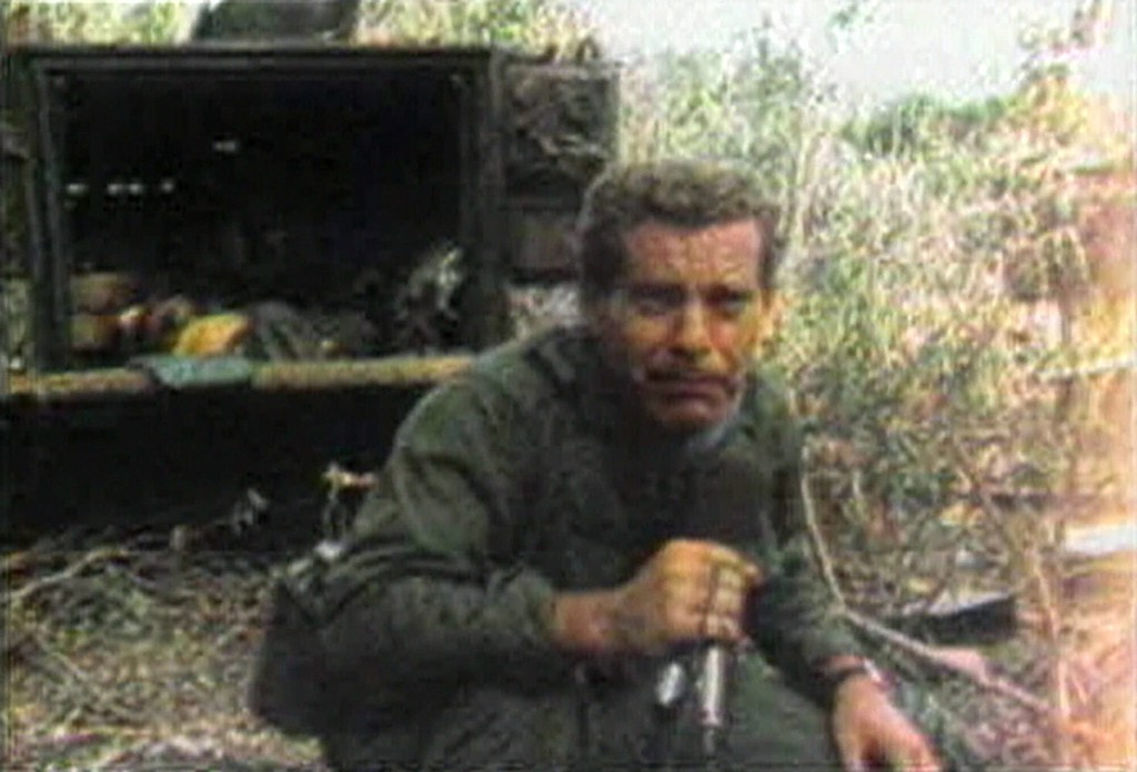 . CBS News correspondent Morley Safer crouches to avoid hostile fire as he reports from Vietnam in 1965.  CBS