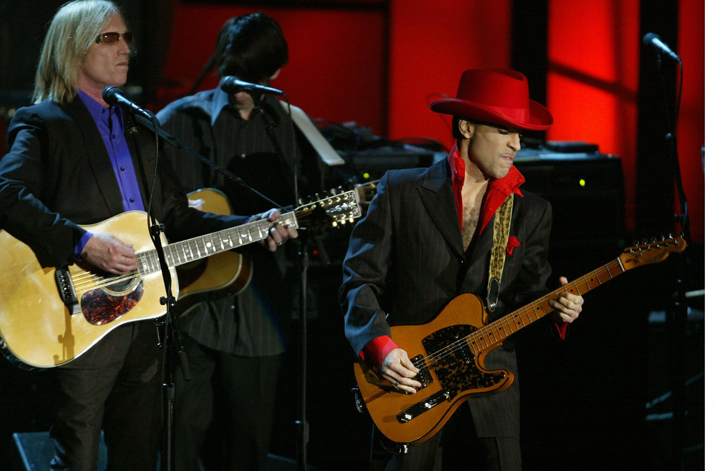 . Inductee Prince performs a song of George Harrison along with Tom Petty after the late Beatle was inducted during the 19th Annual Rock and Roll Hall of Fame Induction Ceremony 15 March 2004 in New York City. (Photo by TIMOTHY A. CLARY/AFP/Getty Images)