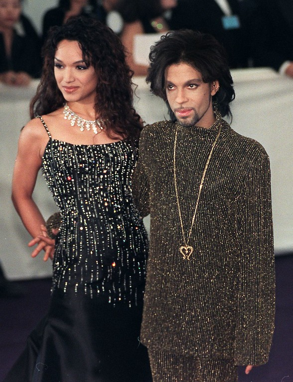". Prince poses for photographers with his wife Mayte as they arrives at the De Beer and Versace ""Diamonds are forever\"" charity fashion event 09 June 1999. A host of international celebrities turned out for the event which will raise funds for three charities including the Prince\'s Foundation for architecture and the environment.  (Photo by SINEAD LYNCH/AFP/Getty Images)"