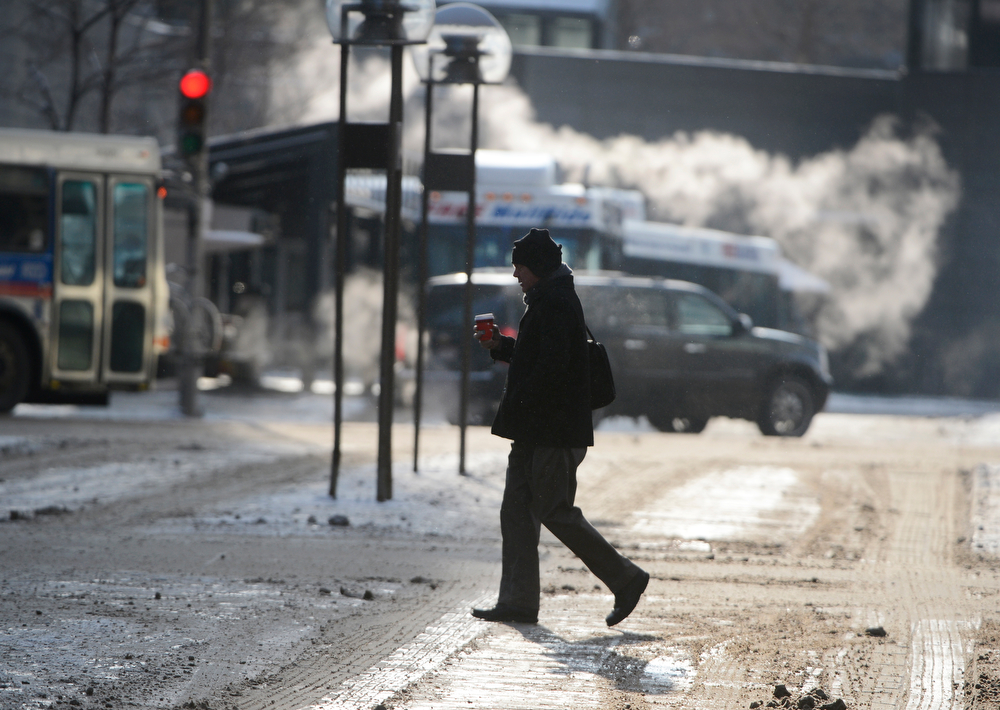 . A pedestrian makes way across the 16th St. Mall, with coffee in hand, in temperatures well below zero Wednesday morning, February 05, 2014. (Photo By Andy Cross / The Denver Post)