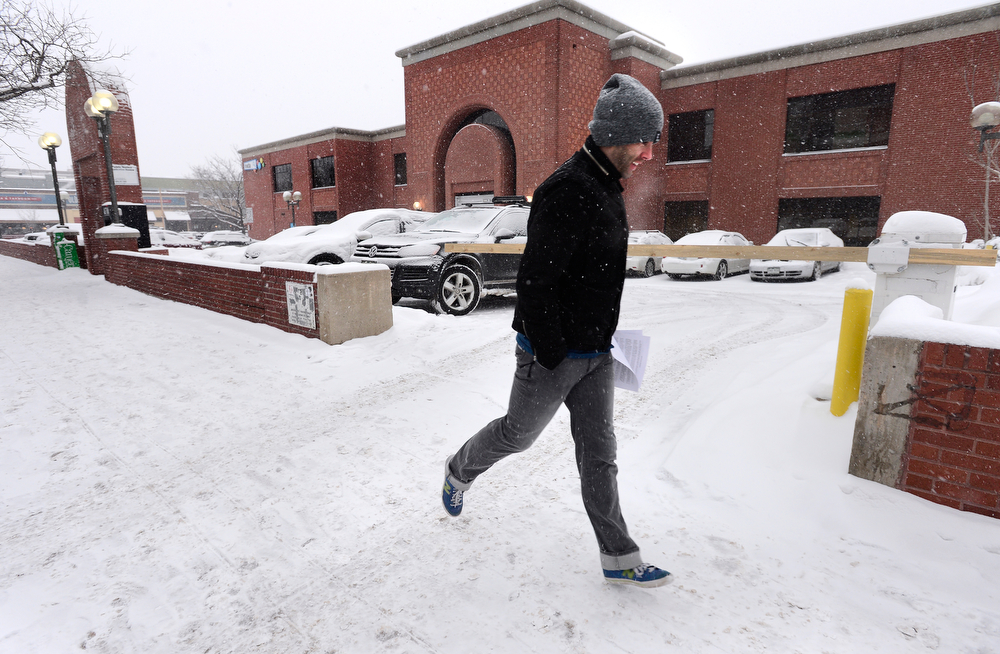 . John Weiss hustles past the 1048 Pearl building as snow falls and a cold wind blows in downtown Boulder on Tuesday evening, February 4, 2014. (Photo by Paul Aiken/The Daily Camera)
