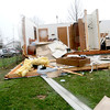 Clinton Omohondro walks alongside a home on East Walker Avenue that had three of its four outside walls torn down on Wednesday, Jan. 30, 2013, in Galatia, Ill. A severe storm ripped through a small part of the Saline County town late Tuesday evening. (AP Photo/The Southern Illinoisan, Paul Newton)