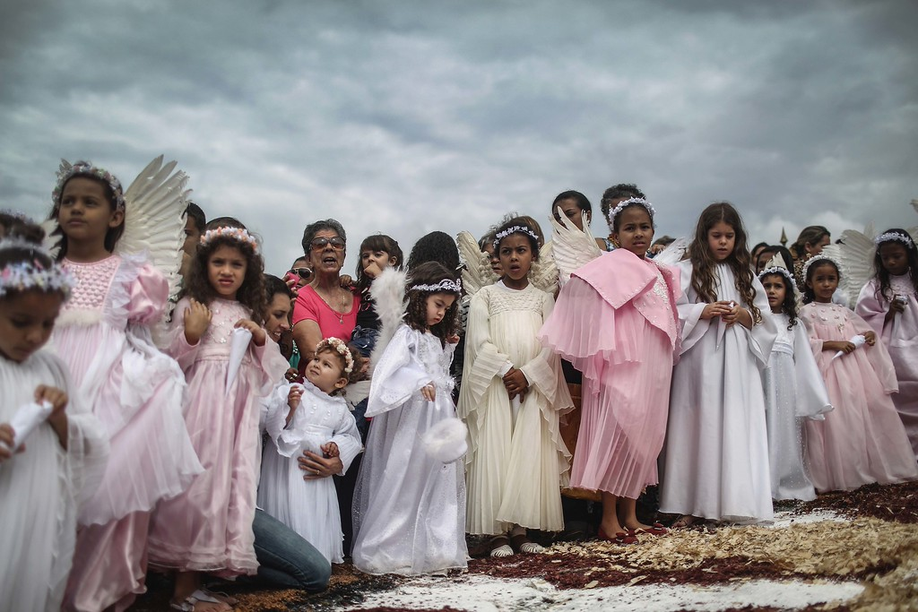 . Girls dressed as angels stand at the annual Easter procession during traditional Semana Santa (Holy Week) festivities on April 5, 2015 in Ouro Preto, Brazil. Holy Week marks Easter celebrations for Catholics and Brazil holds the largest number of Catholics on the planet. Ouro Preto was a colonial mining town founded in the late 17th century and the Semana Santa tradition in Ouro Preto can be traced back to the 18th century Portuguese colonial period.  (Photo by Mario Tama/Getty Images)