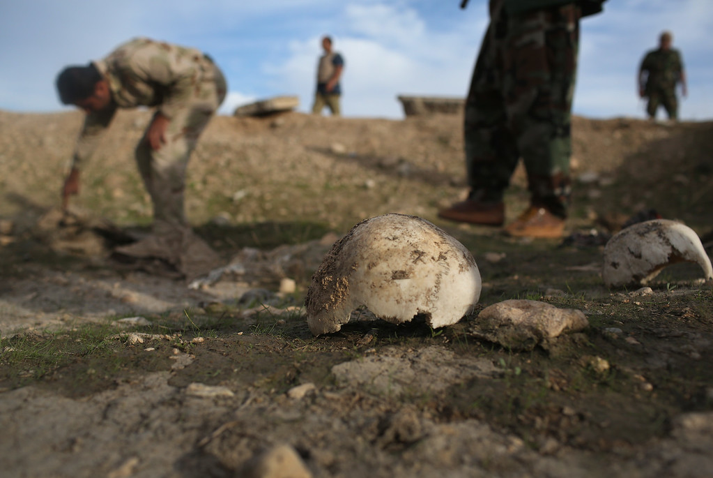 . Kurdish Peshmerga show what they say is a mass grave of more than 50 Yazidis killed by ISIL on November 15, 2015 in Sinjar, Iraq. Kurdish forces, with the aid of massive U.S.-led coalition airstrikes, liberated Sinjar from ISIL extremists, known in Arabic as Daesh, in recent days. Local Yazidi fighters who fought with Kurdish forces have been taking any salvagable items out of the rubble, the town being uninhabitable and perilously close to the frontline.  (Photo by John Moore/Getty Images)