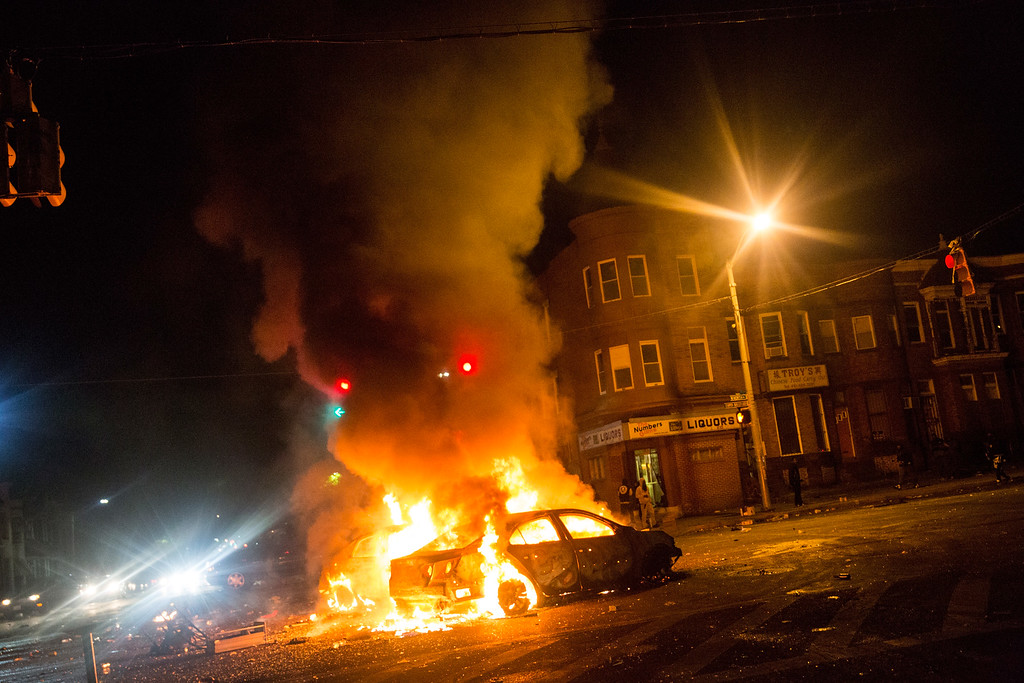 . Two cars burn in the middle of an intersection at New Shiloh Baptist Church on April 27, 2015 in Baltimore, Maryland. Riots have erupted in Baltimore following the funeral service for Freddie Gray, who died last week while in Baltimore Police custody.  (Photo by Andrew Burton/Getty Images)