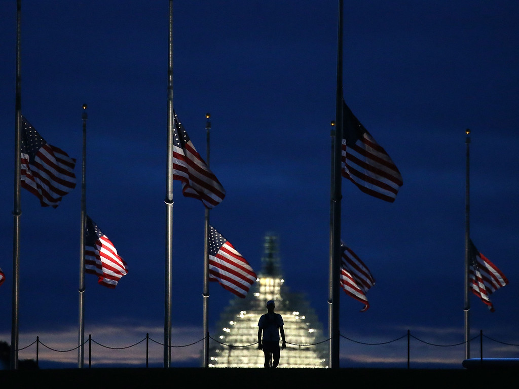 . A man walks past a row of American flags that have been lowered to half staff on the Washington Monument grounds, near the US Capitol on September 11, 2015 in Washington, DC. Today marks the fourteenth anniversary of the September 11, 2001 attacks when terroristists high jacked airliners and flew them in the World Trade Center and the Pentagon.  (Photo by Mark Wilson/Getty Images)