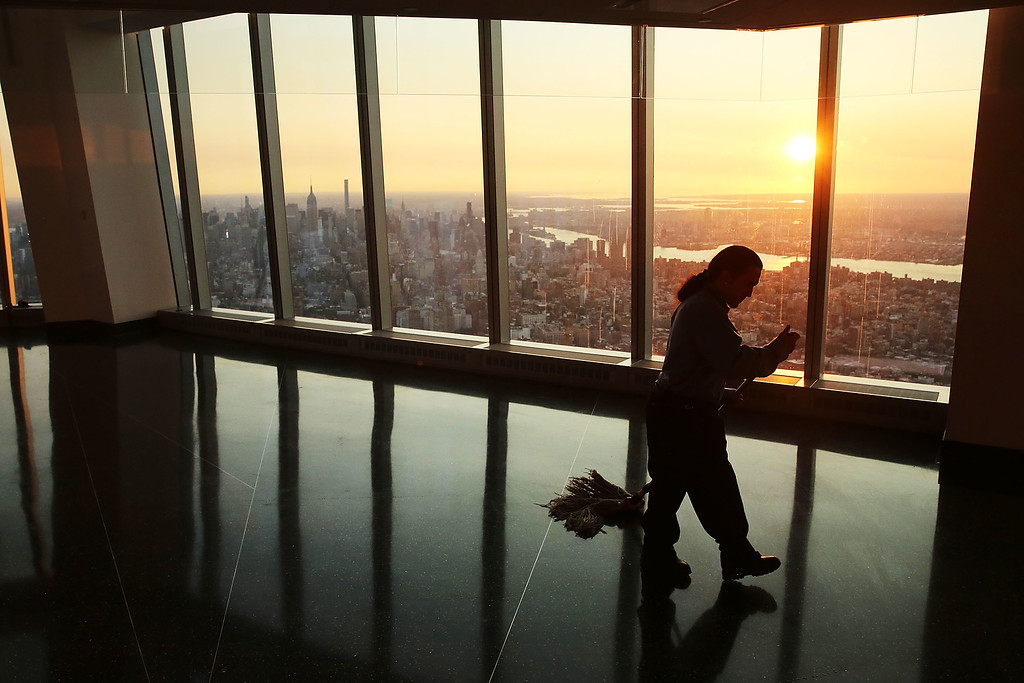 . A custodial worker cleans the floor at dawn at the newly built One World Observatory at One World Trade Center on the day it opens to the public on May 29, 2015 in New York City. The observation deck sits atop the 104-story skyscraper at the former site of the Twin Towers and is expected to become one of Manhattan\'s top tourist attractions.  (Photo by Spencer Platt/Getty Images)